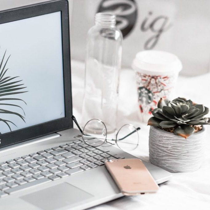 laptop with an empty jar and cactus plant on the side